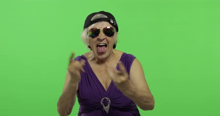 érettség : An elderly woman shouts with a smile and showing tongue. Old pretty happy grandmother in sunglasses and cap. Place for your logo or text. Chroma key. Green screen background