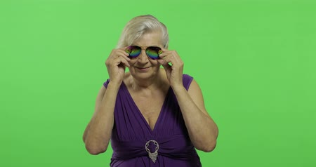 érettség : An elderly woman in sunglasses smiles. Old pretty happy grandmother in a purple dress. Place for your logo or text. Chroma key. Green screen background Stock mozgókép