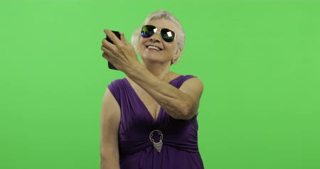érettség : An elderly woman make a photo on a smartphone. Selfie. Old pretty grandmother in a purple dress. Place for your logo or text. Chroma key. Green screen background Stock mozgókép