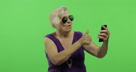 maturità : An elderly woman talks on a smartphone. Having video chat using smartphone. Old pretty grandmother in a purple dress. Place for your logo or text. Chroma key. Green screen background Filmati Stock