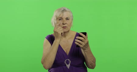gesticulation : An elderly woman works on a smartphone. Old pretty grandmother in a purple dress. Place for your logo or text. Chroma key. Green screen background Stock Footage