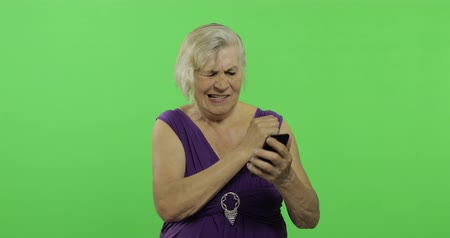 érettség : An elderly woman works on a smartphone. Not satisfied with the result. Old pretty grandmother in a purple dress. Place for your logo or text. Chroma key. Green screen background