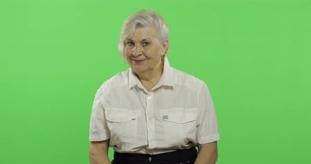 madurez : An elderly woman waving to camera and smiles. Old pretty grandmother in a white shirt. Place for your logo or text. Chroma key. Green screen background Archivo de Video