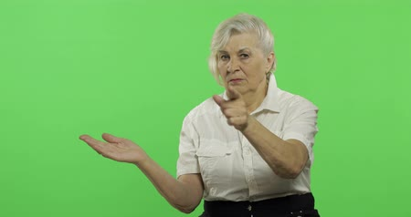madurez : An elderly woman points at something and smiles. Old pretty grandmother in a white shirt. Place for your logo or text. Chroma key. Green screen background