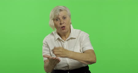 érettség : An elderly woman quarrels at someone. Old unkind grandmother scolding in a white shirt. Place for your logo or text. Chroma key. Green screen background Stock mozgókép