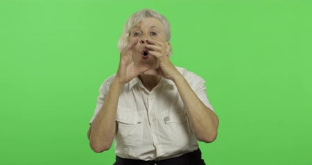 érettség : An elderly woman shout and waving with hands. Old pretty grandmother in a white shirt. Place for your logo or text. Chroma key. Green screen background Stock mozgókép