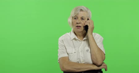 érettség : An elderly woman talks on a smartphone. Old pretty grandmother in a white shirt. Place for your logo or text. Chroma key. Green screen background