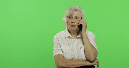 gesticulation : An elderly woman talks on a smartphone. Old pretty grandmother in a white shirt. Place for your logo or text. Chroma key. Green screen background