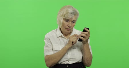 érettség : An elderly woman works on a smartphone. Old pretty grandmother in a white shirt. Place for your logo or text. Chroma key. Green screen background