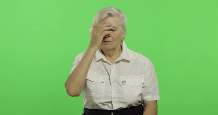 érettség : An elderly woman suffer by headache pain trouble. Old pretty grandmother in a white shirt. Place for your logo or text. Chroma key. Green screen background. Concept of emotions