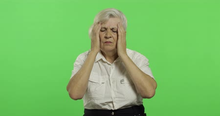 gesticulation : An elderly woman suffer by headache pain trouble. Old pretty grandmother in a white shirt. Place for your logo or text. Chroma key. Green screen background. Concept of emotions