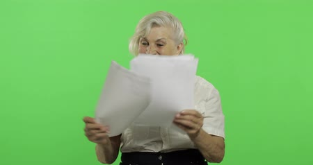 érettség : An elderly woman shows amazement, joy and smiles. Old pretty happy grandmother in a white shirt. Place for your logo or text. Chroma key. Green screen background. Concept of emotions