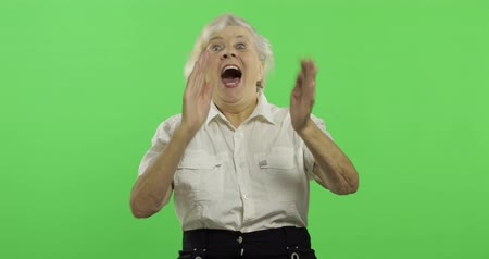 gesticulation : An elderly woman shows amazement, joy and smiles. Old pretty happy grandmother in a white shirt. Place for your logo or text. Chroma key. Green screen background. Concept of emotions