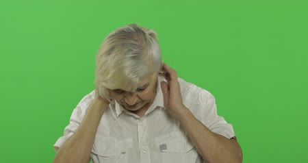 érettség : An elderly woman having pain in neck trouble. Old pretty grandmother in a white shirt. Place for your logo or text. Chroma key. Green screen background. Concept of emotions