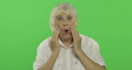 érettség : An elderly woman shows amazement, surprise, joy and smiles. Old pretty happy grandmother in a white shirt. Place for your logo or text. Chroma key. Green screen background. Concept of emotions Stock mozgókép