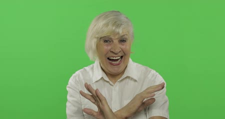 érettség : Joyful elderly lady is laughing. Old pretty happy grandmother in a white shirt. Place for your logo or text. Chroma key. Green screen background Stock mozgókép