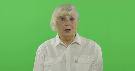 érettség : An elderly woman shows amazement, surprise. Old pretty happy grandmother in a white shirt. Place for your logo or text. Chroma key. Green screen background. Concept of emotions Stock mozgókép