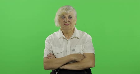 madurez : An elderly woman with crossed arms. Looks at camera and shakes her head. Old grandmother in a white shirt. Place for your logo or text. Chroma key. Green screen background. Concept of emotions