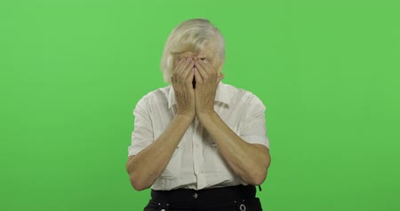 érettség : An elderly woman cries. Senior sed pretty grandmother in a white shirt. Place for your logo or text. Chroma key. Green screen background. Concept of emotions