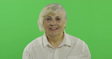 madurez : Joyful elderly lady smiles. Old pretty happy grandmother in a white shirt. Place for your logo or text. Chroma key. Green screen background Archivo de Video