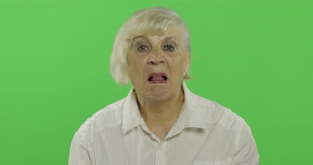 gesticulation : An elderly woman shows tongue. Old pretty happy grandmother in a white shirt. Place for your logo or text. Chroma key. Green screen background. Concept of emotions