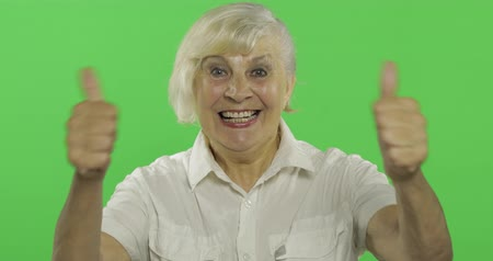 érettség : An elderly woman show thumb up and smiles. Old pretty grandmother in a white shirt. Place for your logo or text. Chroma key. Green screen background