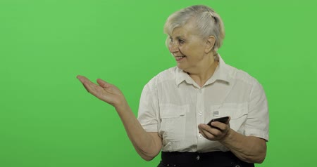 érettség : An elderly woman points at something presenting with open hand palm and smiles. Old pretty grandmother in a white shirt. Place for your logo or text. Chroma key. Green screen background