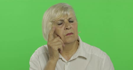 madurez : An elderly woman thinks about something. Old thoughtful grandmother in a white shirt. Place for your logo or text. Chroma key. Green screen background