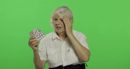 érettség : An elderly woman dissatisfied looking at blister pills. Old pretty grandmother in a white shirt. Place for your logo or text. Chroma key. Green screen background. Concept of emotions
