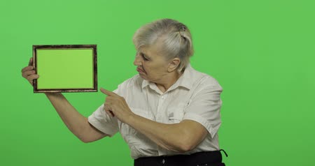 érettség : An elderly woman holding a frame with green image. Old pretty grandmother in a white shirt. Place for your logo or text. Chroma key. Green screen background. Concept of emotions Stock mozgókép