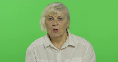 érettség : An elderly woman showing shh gesture. Keeping a secret or asking for silence. Old pretty grandmother in a white shirt. Place for your logo or text. Chroma key. Green screen background