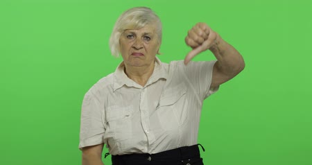 gesticulation : An elderly woman showing no and giving her thumb down. Old pretty grandmother in a white shirt. Place for your logo or text. Chroma key. Green screen background