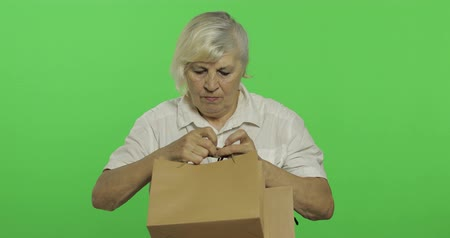 madurez : An elderly woman with shopping bags. Shopping. Presents. Old pretty grandmother in a white shirt. Place for your logo or text. Chroma key. Green screen background