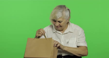 gesticulation : An elderly woman with shopping bags. Happy after shopping. Presents. Old pretty grandmother in a white shirt. Place for your logo or text. Chroma key. Green screen background