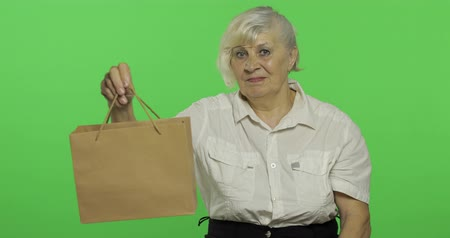 érettség : An elderly woman with shopping bag. Looks into the camera and stretches the gift. Shopping. Old pretty grandmother in a white shirt. Place for your logo or text. Chroma key. Green screen background