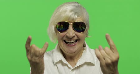 érettség : An elderly woman show sign of the horns with her hands. Old pretty happy grandmother in sunglasses and white shirt. Place for your logo or text. Chroma key. Green screen background Stock mozgókép