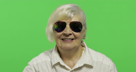 érettség : An elderly woman in sunglasses show thumb up and smiles. Old pretty grandmother in a white shirt. Place for your logo or text. Chroma key. Green screen background Stock mozgókép