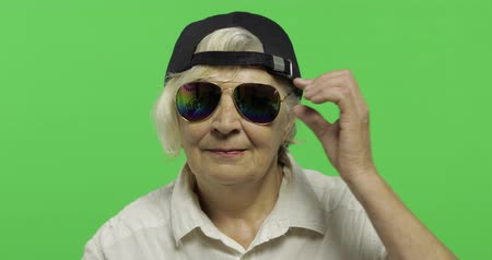 gesticulation : An elderly woman in sunglasses and cap smiles. Old pretty happy grandmother in a white shirt. Place for your logo or text. Chroma key. Green screen background Stock Footage