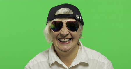 érettség : An elderly woman in sunglasses and cap smiles. Laughing. Old pretty happy grandmother in a white shirt. Place for your logo or text. Chroma key. Green screen background