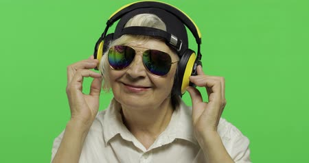 ouvir : An elderly woman listens to music in headphones and dances. Old pretty happy grandmother in sunglasses and cap. Place for your logo or text. Chroma key. Green screen background