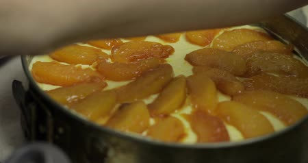 ciasta : Preparation of cheesecake. Putting pieces of caramelized peaches on mixed cottage cheese and chicken eggs