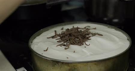 produtos lácteos : Preparation of cheesecake. Adding chocolate on cake with cream before putting it in the oven Vídeos