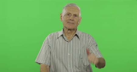 rebuliço : Senior man show thumb up and smiles. Handsome old man on chroma key background. Positive elderly grandfather in grey shirt. Place for your logo or text. Chroma key. Green screen background