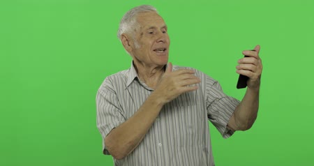 вырезка : Senior man talks on a smartphone. Having video chat using smartphone. Handsome old man on chroma key background. Grandfather in grey shirt. Chroma key. Green screen background