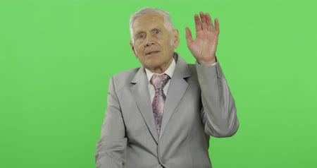 substituição : Elderly businessman waving with hands to camera. Old man in formal wear on chroma key background. Place for your logo or text. Green screen background