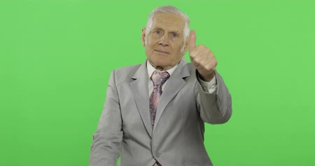 yedek : Elderly businessman giving thumb up. Old man in formal wear showing thumb up gesture on chroma key background. Symbol of agreement and success. Green screen background