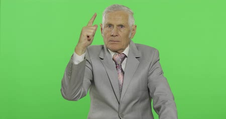 substituição : Elderly businessman quarrels at someone threateningly moves with his hand. Old man in formal wear on chroma key background. Place for your logo or text. Green screen background