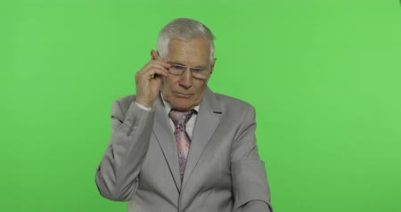 substituição : Elderly businessman in suit thinks about something. Old thoughtful senior man in formal wear on chroma key background. Place for your logo or text. Green screen background