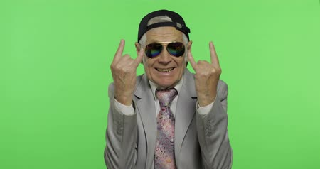 yedek : Funny elderly businessman in sunglasses and cap show sign of the horns with his hands. Old man in formal wear on chroma key background. Place for your logo or text. Green screen background