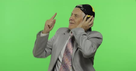 stary : Funny elderly businessman listens to music in headphones and dances. Old man in formal wear and cap chroma key background. Place for your logo or text. Green screen background